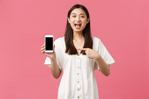 Красота, эмоции людей и концепция технологии. взволнованная симпатичная молодая женщина объявляет, указывая пальцем на дисплей мобильного телефона и взволнованно улыбаясь, показывая потрясающее приложение