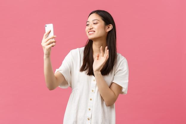 아름다움, 사람들의 감정과 기술 개념입니다. 행복한 아름다운 아시아 소녀가 비디오 채팅에서 친구들과 이야기하고, 스마트폰 카메라를 흔들며 비디오 녹화 메시지로 인사하며 쾌활하게 웃고 있습니다.