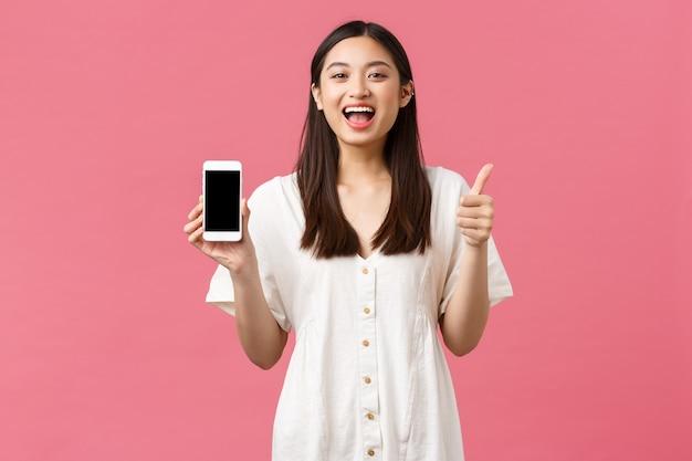 美しさ、人々の感情と技術の概念。満足している幸せなアジアの女の子は、携帯電話の画面アプリケーションを示すように親指を立て、立っているピンクの背景はアプリをお勧めします