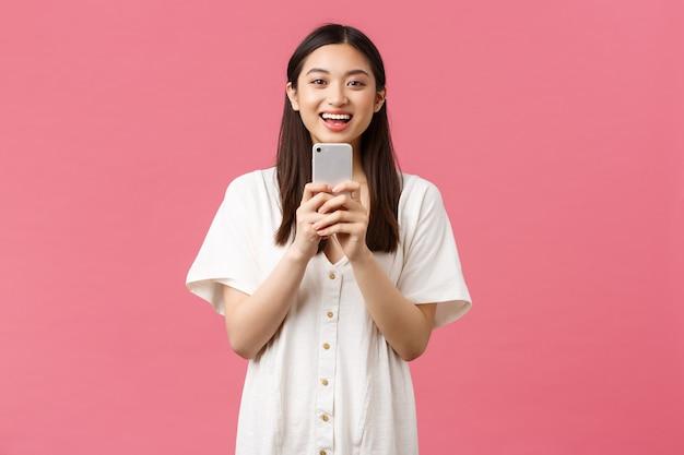 Красота, эмоции людей и концепция технологии. улыбается счастливая азиатская женщина-блоггер, стильная девушка, фотографирующая на смартфоне, оптимистичная, как фотографирующая, фотографирующая с мобильного телефона.