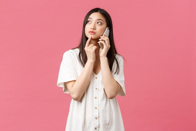 Красота, эмоции людей и концепция технологии. задумчивая азиатская девушка делает доставку заказа с помощью смартфона, думая во время разговора по телефону, глядя вверх, размышляя о выборе, розовый фон