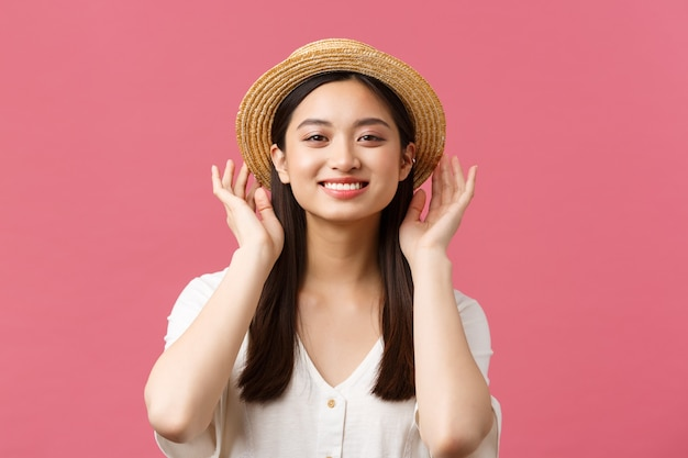 Beauty, people emotions and leisure and vacation concept. lovely asian woman shopping in store, picking new straw hat, smiling delighted, buying summer outfit over pink background
