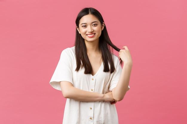 Bellezza, emozioni delle persone e concetto di svago estivo. spensierata ragazza coreana carina in abito bianco, sorridente e toccante ciocca di capelli con sguardo sognante e felice, in piedi sfondo rosa