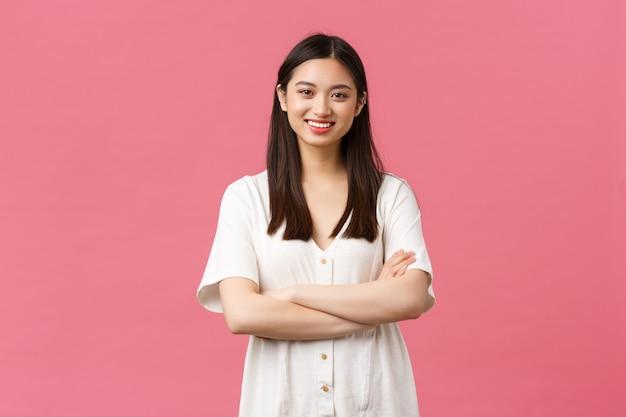 Bellezza, emozioni delle persone e concetto di svago estivo. ragazza asiatica sciocca e allegra in abito bianco, braccia incrociate sul petto, sorridente felice alla telecamera, sfondo rosa in piedi entusiasta.