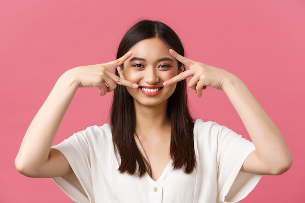 Beauty, people emotions and summer leisure concept. close-up of kawaii smiling tender woman in white dress, showing peace sign over eyes and grinning with white teeth, pink background.