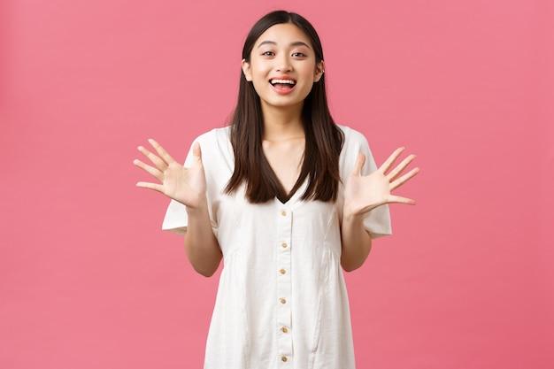 Bellezza, emozioni delle persone e concetto di svago estivo. una ragazza asiatica affascinante e affascinante descrive notizie fantastiche, gesticolando, alzando le mani e sorridendo come un grande annuncio, sfondo rosa.
