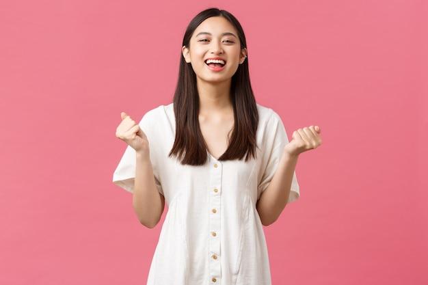 Bellezza, emozioni delle persone e concetto di svago estivo. la ragazza asiatica carina soddisfatta e sollevata sente il gusto del successo, stringe le mani dicendo di sì e sorridendo con gli occhi chiusi, trionfando.
