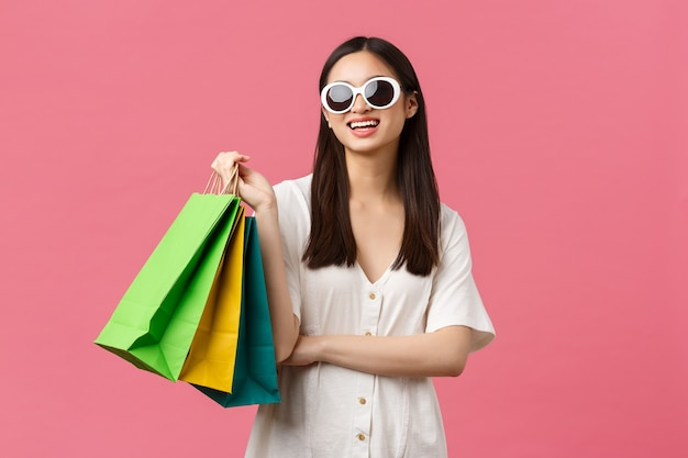 Beauty, people emotions and summer leisure and vacation concept. carefree happy asian girl on vacation, tourist holding shopping bags and wearing sunglasses, smiling satisfied, pink background
