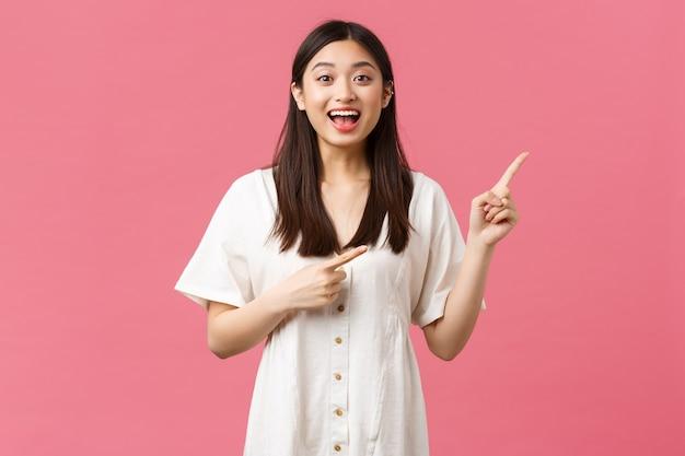 Bellezza, emozioni delle persone e tempo libero estivo e concetto di vacanza. eccitata ed elettrizzata ragazza giapponese carina che punta le dita nell'angolo in alto a destra, in piedi su sfondo rosa in abito bianco.