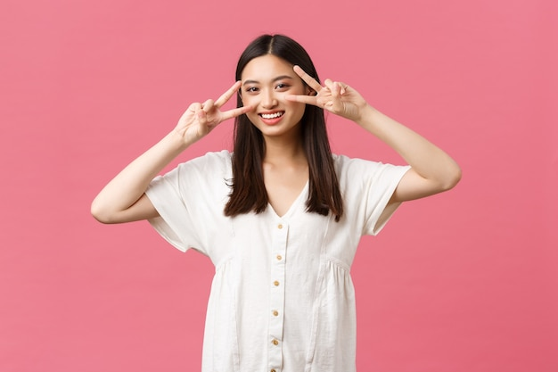 Beauty, people emotions and summer leisure and vacation concept. pretty glamour and cute asian girl showing peace kawaii gestures near face and smiling, advertise skincare or cosmetics product.