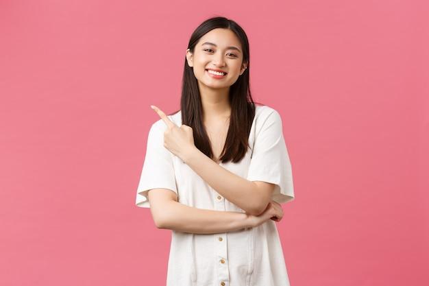 Bellezza, emozioni delle persone e tempo libero estivo e concetto di vacanza. tenera bella ragazza asiatica in abito bianco che punta il dito nell'angolo in alto a sinistra, invitando a dare un'occhiata a una nuova offerta promozionale, sfondo rosa.