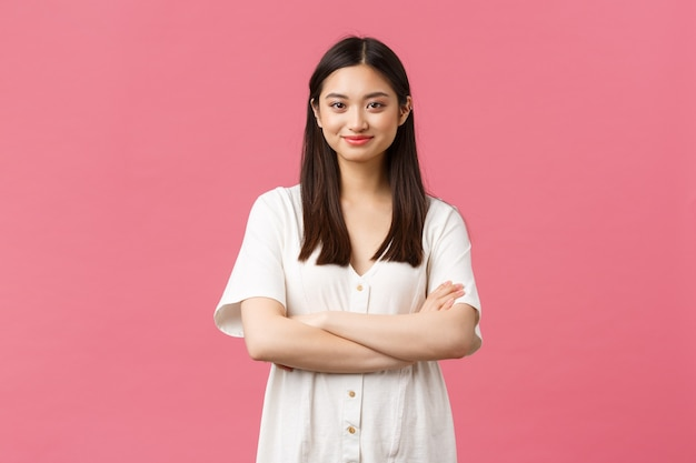 Beauty, people emotions and summer lifestyle concept. tender young asian girl in cute dress smiling camera, standing with crossed hands and professional determined look, pink background.