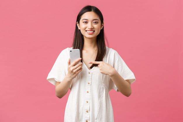 Bellezza, emozioni delle persone e concetto di tecnologia. piacevole bella ragazza asiatica in abito bianco che punta il dito sullo smartphone come trovata un'applicazione fantastica, consiglia l'app per cellulare