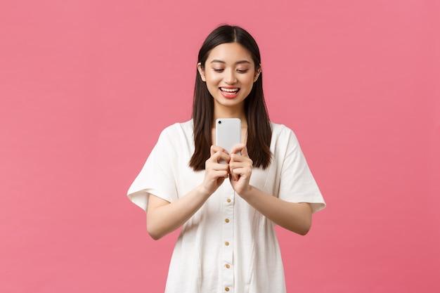 Bellezza, emozioni delle persone e concetto di tecnologia. blogger femminile asiatico felice sorridente, ragazza alla moda che prende foto sullo smartphone, guardando ottimista come fotografare, scattare foto con il telefono cellulare.