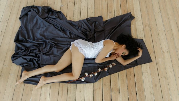 Beauty, people and health, anti-racism concept -beauty closeup portrait of beautiful mixed race woman. beautiful young african american woman cotton branch, woman lies on the floor on a black sheet
