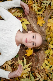 Beauty, people, season and health concept - pretty girl is lying in yellow autumn leaves
