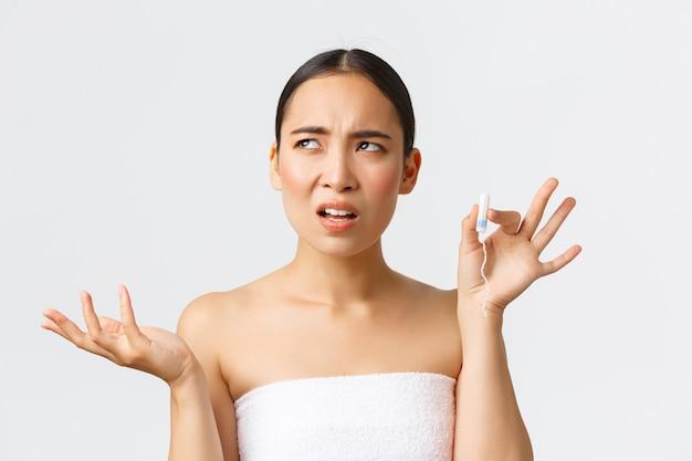 Понятие менструальной гигиены красоты, личного и интимного ухода. смущенная и недовольная азиатская женщина в банном полотенце жалуется на тампоны, поднимает руку и смотрит в сторону, пользуется менструальными чашками.