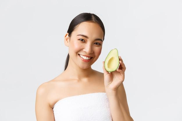 미용, 퍼스널 케어, 스파 및 스킨 케어 개념. 아보카도를 보여주고 웃고있는 목욕 타월에 아름다운 아시아 여성의 근접 촬영, 얼굴 마스크 또는 얼굴 보습 및 영양 크림을 권장합니다.