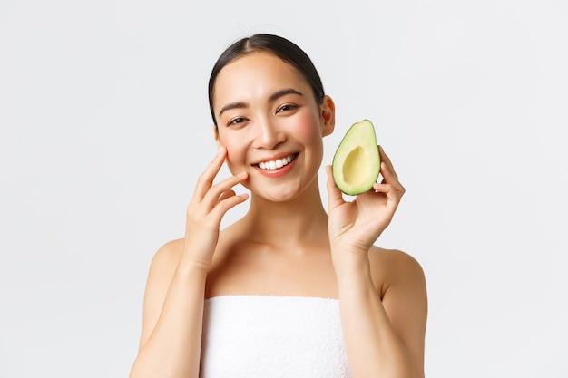 미용, 퍼스널 케어, 스파 및 스킨 케어 개념. 부드럽게 얼굴을 만지고 아보카도를 보여주는 목욕 타월의 아름다운 아시아 여성의 근접 촬영은 영양가있는 얼굴 마스크, 클렌저 또는 크림을 권장합니다.