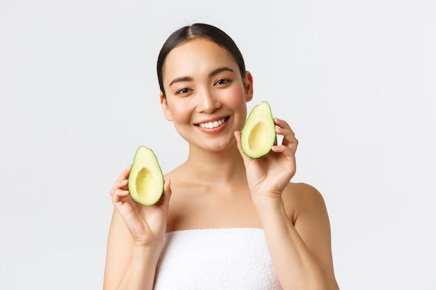 미용, 퍼스널 케어, 스파 및 스킨 케어 개념. 목욕 타월에 부드러운 여성 아시아 여자, 미소하고 얼굴 근처 아보카도, 얼굴 마스크, 클렌저 또는 크림의 광고를 보여주는 근접.