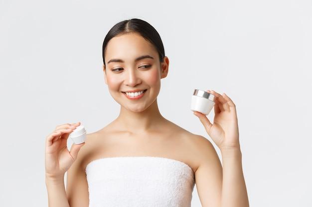 美容、パーソナルケア、スパサロン、スキンケアコンセプト。 2つのクリーム、目と顔の栄養製品、笑みを浮かべて、皮膚の治療を保持しているバスタオルで美しいアジアの女性のクローズアップ