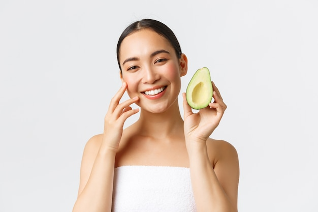 Beauty, personal care, spa and skincare concept. close-up of beautiful asian woman in bath towel gently touching face and showing avocado as recommend nourishing face mask, cleanser or cream.