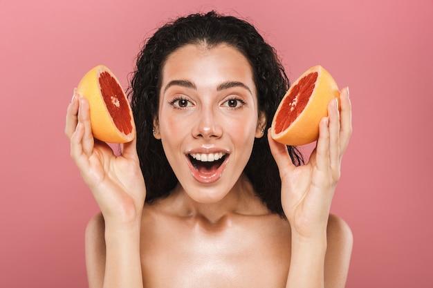 ピンクの背景で隔離の長い髪の笑顔とグレープフルーツの断片を保持しているヨーロッパのブルネットの女性の美しさの写真