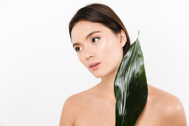 Beauty picture of feminine asian woman with black arrows looking aside while holding green leaf, isolated over white
