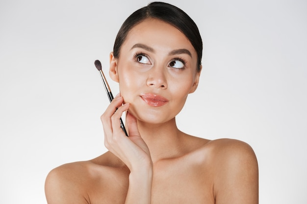 Beauty picture of gorgeous woman with hair in bun looking upward and holding brush for eyeshadow, isolated over white