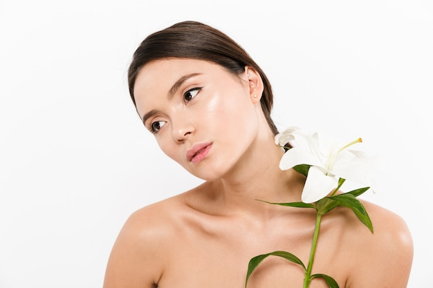 Beauty picture of half-naked asian woman looking aside and holding beautiful flower in hand, isolated over white