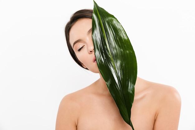 白で分離された緑の葉で彼女の顔を覆っている目を閉じて半分裸のアジアの女性の美しさの写真