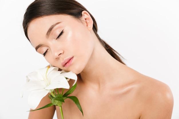 白で分離された美しい花を手で押し、目を閉じて半分裸のアジアの女性の美しさの写真