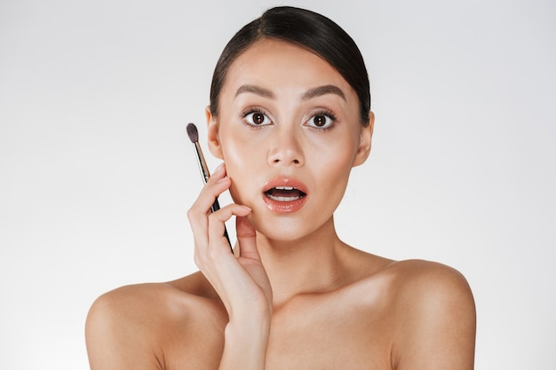 Beauty picture of surprised woman with open mouth looking on camera and holding brush for eyeshadow, isolated over white