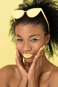 Ritratto di bellezza della donna afro con lucidalabbra giallo e occhiali da sole