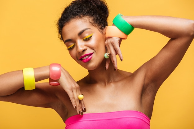 Beauty portrait of attractive african american woman with fashion makeup and jewelry on hands posing isolated, over yellow wall