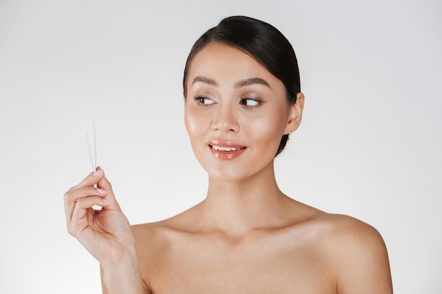 Beauty portrait of attractive candid dark-haired woman looking at small tweezers holding in her hand, isolated over white