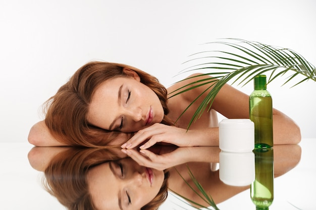 Beauty portrait of attractive ginger woman with long hair lying on mirror table with closed eyes near the bottle of lotion