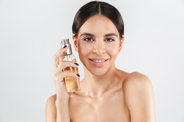 Beauty portrait of an attractive healthy woman standing isolated over white wall, applying body oil