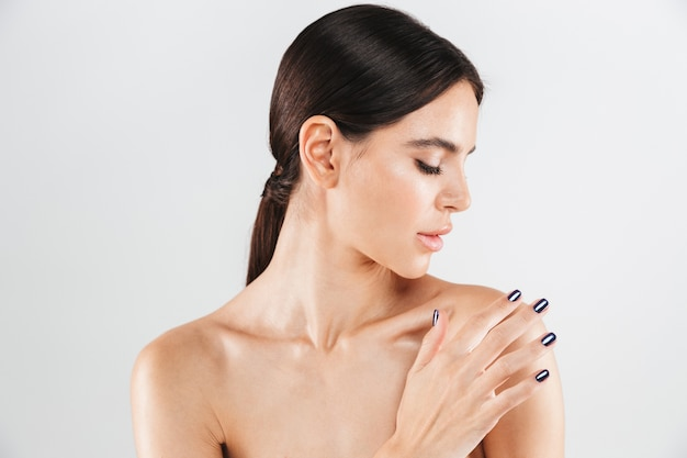 Beauty portrait of an attractive healthy woman standing isolated over white wall, applying moisturizer on her shoulder