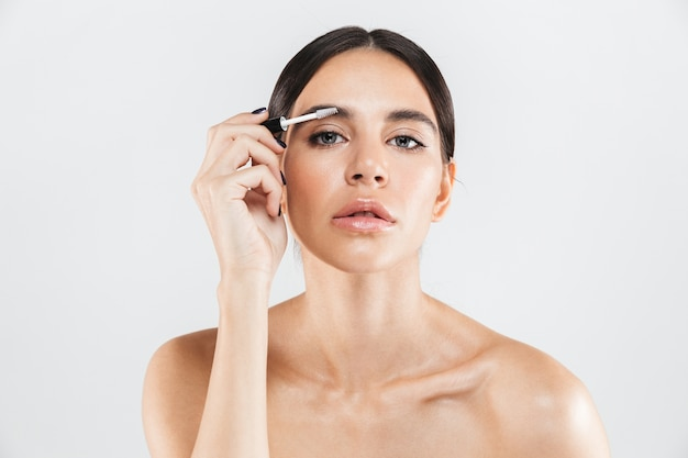 Beauty portrait of an attractive healthy woman standing isolated over white wall, doing her eyebrows