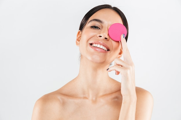 Beauty portrait of an attractive healthy woman standing isolated over white wall, showing makeup sponge
