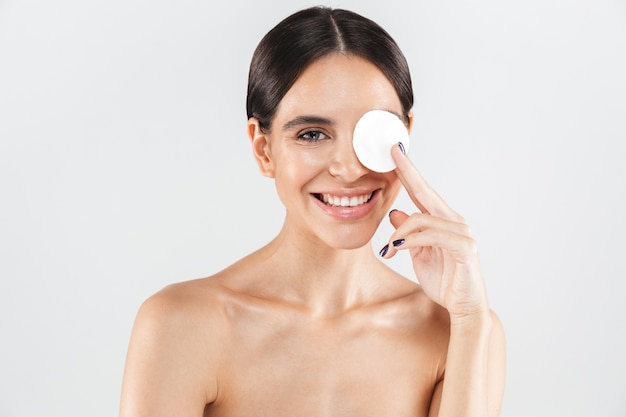 Beauty portrait of an attractive topless woman removing her makeup with a cotton pad isolated over white wall