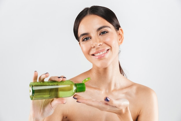 Beauty portrait of an attractive woman holding body lotion isolated over white wall