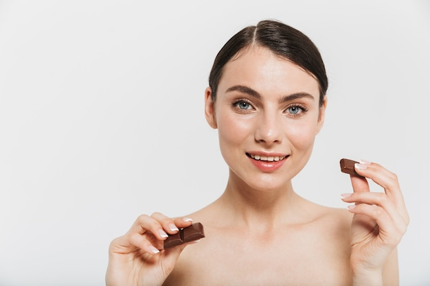 Beauty portrait of an attractive young brunette woman standing isolated over white wall, showing black chocolate bar
