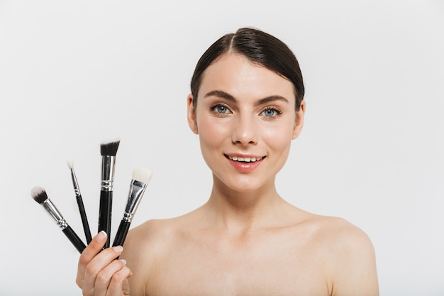 Beauty portrait of an attractive young brunette woman standing isolated over white wall, showing make-up brushes