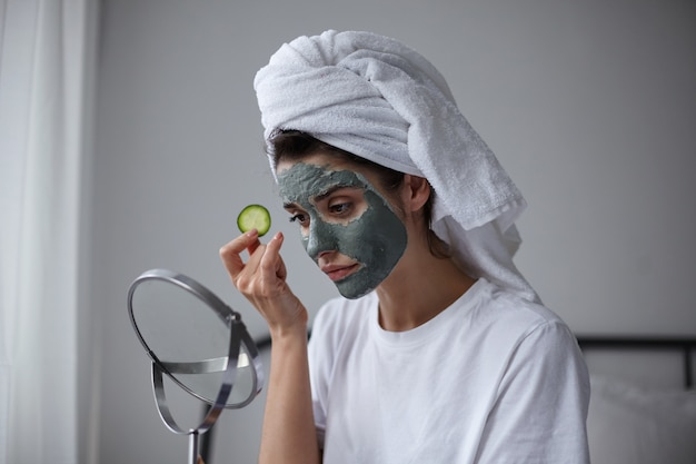 Beauty portrait of attractive young dark haired calm female in moisturizing mask with fresh cucumber in her hand looking into mirror, keeping lips folded while posing over home interior