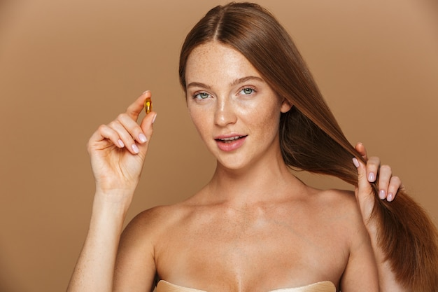 Beauty portrait of a beautiful healthy young  woman with long red hair showing vitamin capsule isolated over beige wall