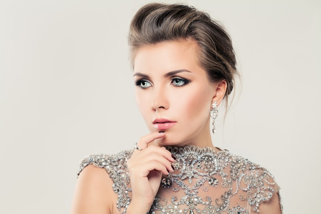 Beauty portrait of blonde woman with earings and silver dress and glam makeup on white background