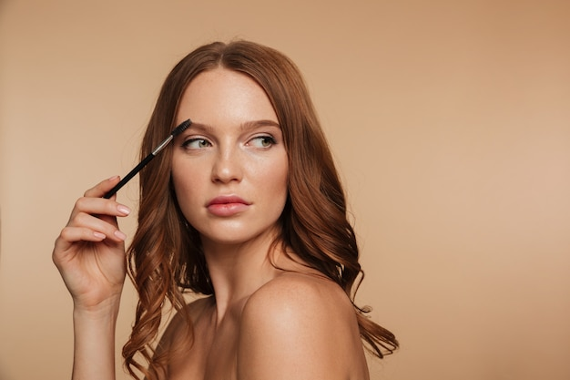 Beauty portrait of calm ginger woman with long hair looking away and posing sideways while combing her eyebrows with brush