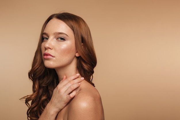Beauty portrait of calm ginger woman with long hair posing sideways and looking